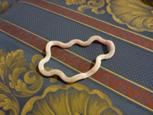 Image Description: a rose-pink Fuzzy Tangle Jr expanded to resemble a circle, lying flat on top of a couch cushion, which is navy blue with gold-coloured fleur-de-lis pattern printed on it.