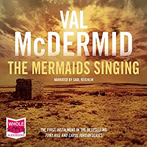 Image Description: book-cover of the Auido-book format of The Mermaids Singing by Val McDermid. The title text and the author text (in white) take up most of the cover, the cover has a yellow sepia-tint to it, but I think it's a picture of farm-yard or pasture with a delapidated brick building in it.