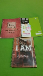 Image Description: Three A4 sized notebooks. From left to right, a book with a red cover with a pale white square with the words '192 Meh' beneath the square is displayed text 'The Element of Apathy'. To the right of that notebook, there is a standard green Marbig 200 page lecture book with colour-hide cover. Beneath them both, there is a cover with a picture of a collection of suburban buildings that look like flats and or units with large white-text printed over the top 'I AM Self-Made'