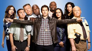 Image Description: The background is periwinkle-blue, with the full cast of Brooklyn 99 standing in front it. From left to right: Gina Linetti, Charles Boyle, Norman Scully, Captain Raymond Holt, Jake Peralta, Terry Jeffords, Amy Santiago, Rosa Diaz, and Michael Hitchcock