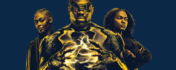 Image Description: a medium-sized banner picture. The background is navy blue. In the foreground is a trio of people (posing Charlie's Angels style) with a yellow-sepia tinted colour over the image. The three people from left to right:  Anissa Pierce/Thunder, Jefferson Pierce/Black Lightning, and Jennifer Pierce.